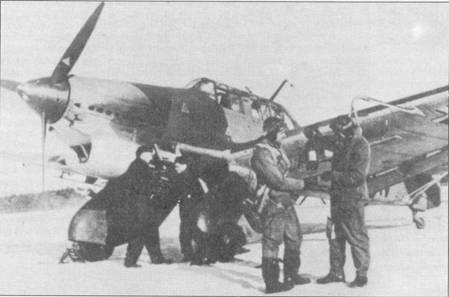 Двое летчиков-пикировщиков (Stukaflieger) позируют на фоне бомбардировщика. У самолета пара «негров» (так в люфтваффе прозвали за цвет комбинезонов техников) возится с ручкой инерционного стартера запуска двигателя Jumo- 210. Среди прочих внешних отличительных признаков «Антона» являлись «рожки дьявола» — установленные на фонаре кабины две мачты крепления проволочной радиоантенны.