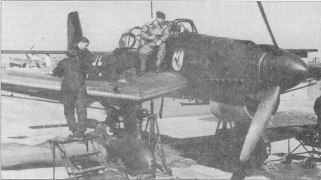 Типичная сценка на полевом аэродроме начального периода второй мировой войны. Летчик — в кабине, рядом пристроился одетый в утепленный комбинезон воздушный стрелок. Техники подготовили самолет к отстрелу крыльевых пулеметов, чем и должен в ближайшие минуты заняться пилот. Бомбардировщик имеет бортовой код «S2+EN» и принадлежит 5-му стаффелю II/Stukageschwader-77; кок винта — красный. Бомбардировщики 5-го стаффеля несли на обтекателях колес основных опор шасси литеры «Е» красного цвета. Самолеты из II/Stukageschwader-77 принимали участие в трагических налетах на Британские острова, в этих рейдах группа понесла тяжелейшие потери.