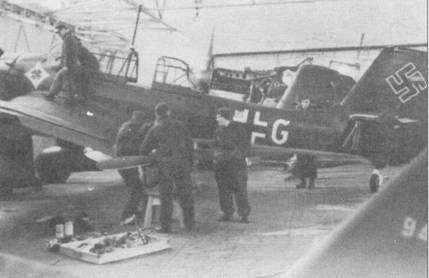 Из-за слабого контраста черно-зеленого и темно-зеленого цветов на чернобелых фотографиях пикирующих бомбардировщиков Ju-87 создается впечатление будто самолеты имеют сверху и с боков однотонную окраску. Практически всегда на самолеты наносили эмблемы подразделений. Данная машина имеет бортовой код «T6+GM», литера «G» — белого цвета, остальные — черные. Бомбардировщик принадлежит 7./S1.G-2 На заднем плане виден самолет 8-го стаффеля: кок винта красного цвета.