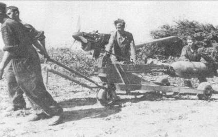 Франция, 1940г. оружейники тянут трехколесный транспортер с бомбой, транспортер оборудован компактным подъемником для бомб. По маркировки на подъемнике «З-St» можно установить, что снимок сделан в расположении 3./Stukageschwader-2.