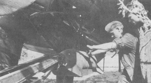 Самолеты модификаций «В-1» и «В-2» имели одинаковую конструкцию рамы, отводящей бомбу от фюзеляжа за пределы ометаемой винтом площади. На снимке — процесс подвески бомбы на раму при помощи трехколесного транспортера- подъемника. За редким исключением рама бомбодержателя красилась в черный или темно-серый цвета.