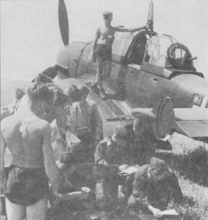 Личный состав одного из стаффелей St.G-77 готовится к очередному боевому вылету. Этот Ju-87B-2 имеет полный комплект штатной бронезащиты, в том числе — бронеперегородку между кабинами летчика и стрелка. В центр шаровой прозрачной установки кормового пулемета вмонтировано бронестекло прямоугольной формы; бронестекло несколько ограничивало обзор стрелка, но увеличивало его шансы когда-нибудь встретиться в фатерлянде со своей гретхен. Броней прикрыты также нижние задние углы фонаря кабины стрелка, в этих местах броня чаще всего красилась в серый цвет. Броня могла быть установлена на пикирующих бомбардировщиках Ju-87B-1 и Ju-87B-2 в полевых условиях посредством использования «комплекта полевой модификации U-3». Очень быстро броня стала стандартной для всех «Штук» и устанавливалась уже на заводе. Отсутствие бронезащиты стало одной из причин высоких потерь в пикирующих бомбардировщиках во время Битвы за Англию.