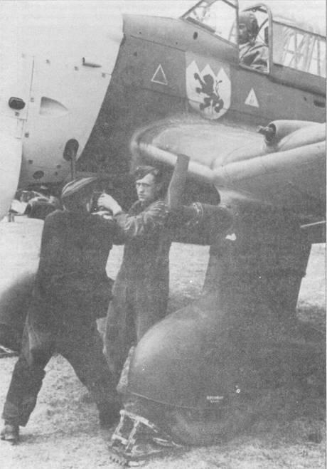 Механики с помощью «ручки дружбы» запускают двигатель бомбардировщика Ju-87B. На снимке хорошо видна эмблема Stab/ll/St.G-77, цвета эмблемы — желтый, красный, черный. Снимок сделан в период кампании на Балканах весной 1941г.