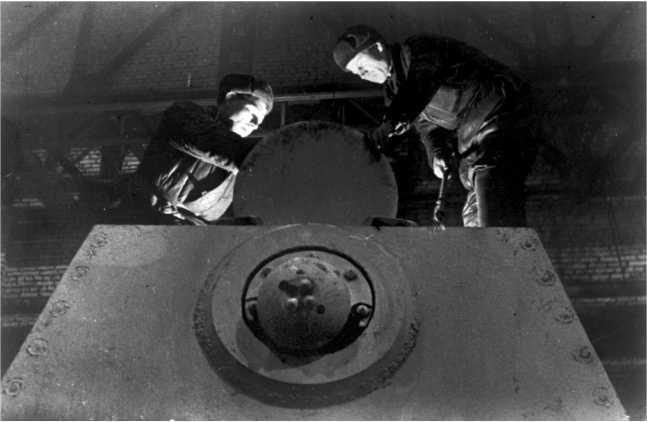 Ремонт танка КВ-1 на одном из московских предприятий. Зима 1941 года. На этом фото хорошо видно дополнительное броневое кольцо защиты пулеметной установки в кормовом листе башни. Такое кольцо встречается на некоторых челябинских КВ-1 со сварными башнями выпуска осени 1941 года (АСКМ).