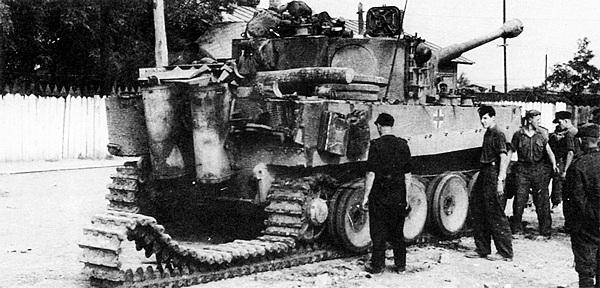 Демонтаж транспортной гусеницы с одного из танков «Тигр» моторизованной дивизии «Великая Германия». Август 1944 года.