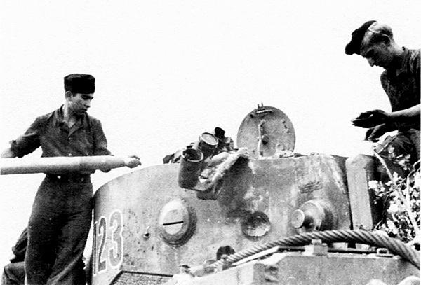 Загрузка боеприпасов в один из танков 503-го тяжёлого танкового батальона. Хорошо видная вмятина от снаряда в борту башни.