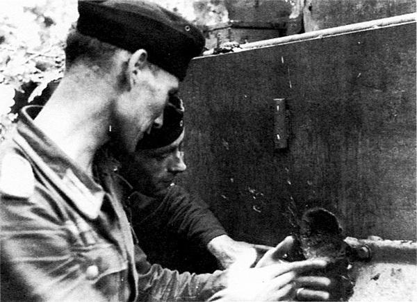 Немецкие танкисты рассматривают след попадания вражеского снаряда в борту своего «Тигра».
