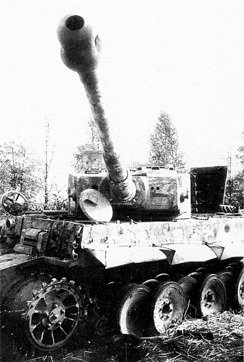 Ещё один подбитый «Тигр», так называемой «промежуточной» модели, выпуска конца 1943 — начала 1944 года. Опорные катки ещё с резиновыми бандажами, но фара уже на лобовом листе, новая командирская башенка, бинокулярный прицел, циммерит…