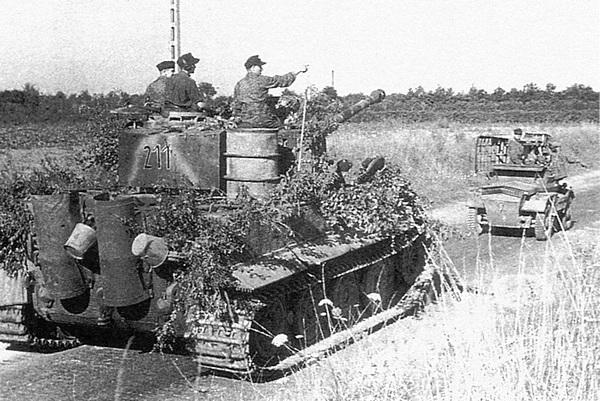 Один из танков 102-го тяжёлого <a href='https://arsenal-info.ru/b/book/348132256/10' target='_self'>танкового батальона</a> СС выдвигается к линии фронта у реки Орн. Нормандия, июль 1944 года.