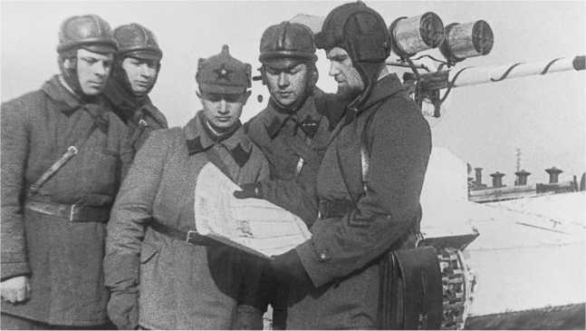 Танкисты получают «боевую задачу». Учения войск МВО, 1936 год. На заднем плане виден Т-26 выпуска 1935 года с установленными на маске пушки фарами боевого света (АСКМ).